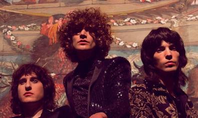Els tres integrants de la banda amb els cabells llargs i arrissats