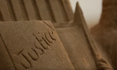 Una imagen de la palabra Justicia escrita sobre una superficie de arena sirve de cartel para anunciar el film