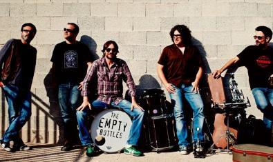 Retrat del grup en exteriors i al voltant d'una bateria amb el nom de la banda