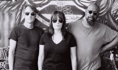 Els tres membres de la banda amb ulleres de sol i davant d'un grafiti