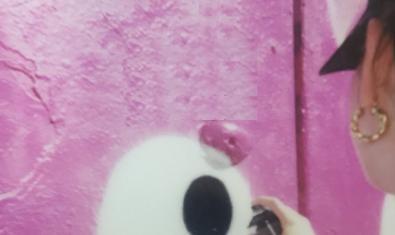 El perfil d'una dona que pinta un grafiti al cartell de l'exposició
