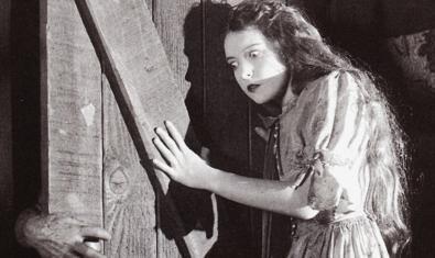 Un fotograma del film en blanco y negro donde se ve a una chica atemorizada cerrando una puerta
