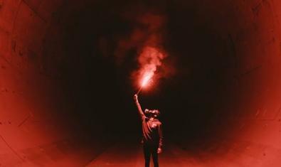 Una imagen de un hombre dentro de un túnel con una antorcha encendida en la mano sirve de cartel para anunciar la sesión