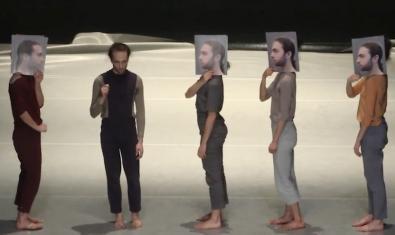 Un momento de la coreografía con los intérpretes en hilera y llevando unas fotografías de rostros que les tapan su auténtica cara