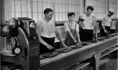 Charles Chaplin y tres compañeros trabajando en la cadena de montaje.