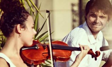Los integrantes del dúo retratados con sus instrumentos en plena actuación