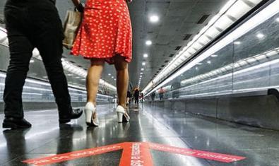 Una imatge genèrica de l'experiència que mostra les cames de dos viatgers caminant al metro sobre un senyal que recorda la necessitat de mantenir la distància de seguretat