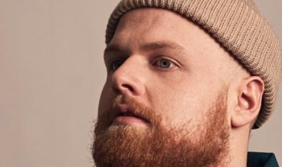 Fotografía del artista con una barba pelirroja y una gorra de lana