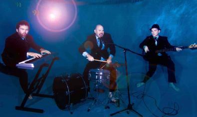 Los tres miembros de la banda descalzos y en plena actuación