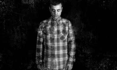 Retrat en blanc i negre del DJ extremeny amb els ulls tancats i vestint una camisa de quadres