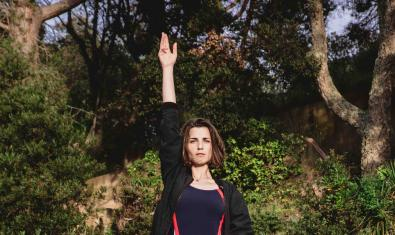 La artista Gemma Planell retratada en un entorno natural con la mano derecha levantada