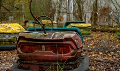 Un parc d'atraccions abandonat amb els autos de xoc rovellats en primer pla