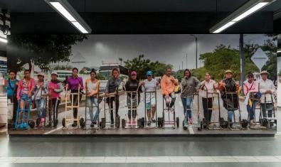 Un gran retrato fotográfico de un grupo de unas quince personas a tamaño natural instalado en un vestíbulo del metro
