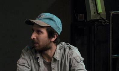 Un dels personatges protagonistes assegut i amb una gorra posada en un moment de la representació