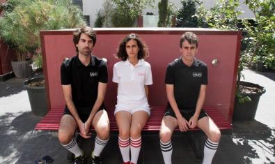 Els tres integrants de la banda, vestits de futbolista i asseguts en un banc