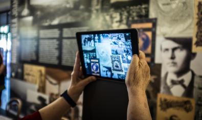 Unas manos haciendo una foto a un mural con una tablet