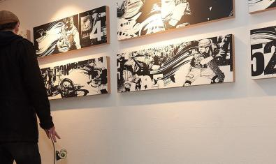 Un visitant es mira les obres de l'artista a l'exposició de la Montana Gallery