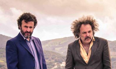 El músico cretense y el músico australiano fotografiados en exteriores con un paisaje de montañas de fondo