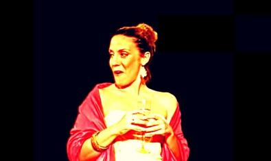 La actriz protagonista vestida de rojo y blanco y con una copa en la mano en un momento de la representación