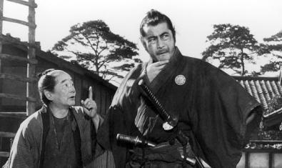 Yojimbo talking to a man, in pensive pose.