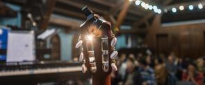 Un primer plano de una guitarra en una sala llena de espectadores