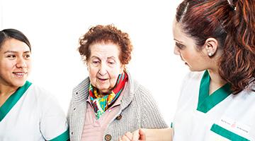 Dos chicas jóvenes vestidas con un uniforme sanitario cogiendo de las manos a una persona anciana