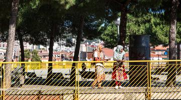 Dues noies amb el cap cobert per un vel miren el carrer recolzades sobre la barana d'un parc