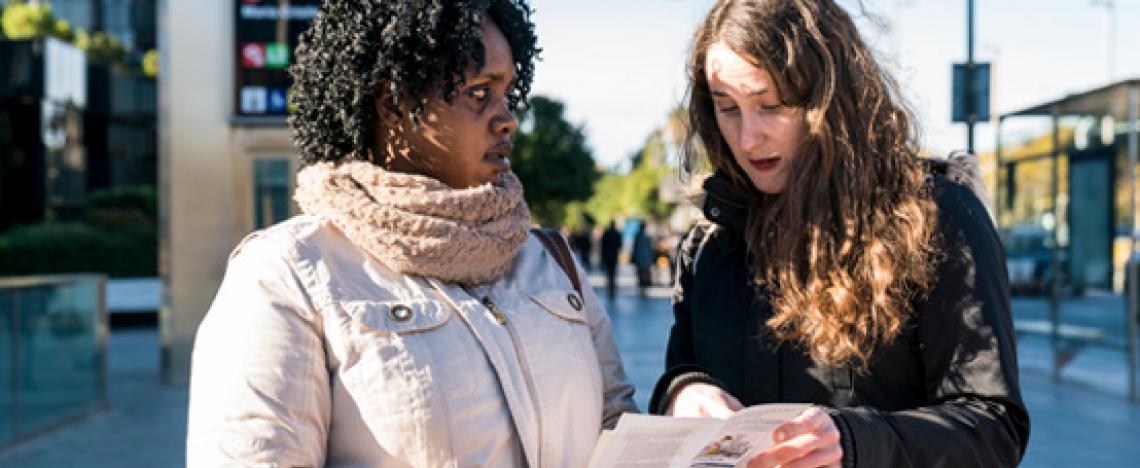 Una treballadora municipal explica un díptic informatiu sobre els drets laborals a una ciutadana que passeja pel carrer.