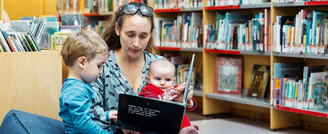 Una mujer, un niño y un bebé sentados sobre unos cojines mirando un álbum ilustrado en una biblioteca