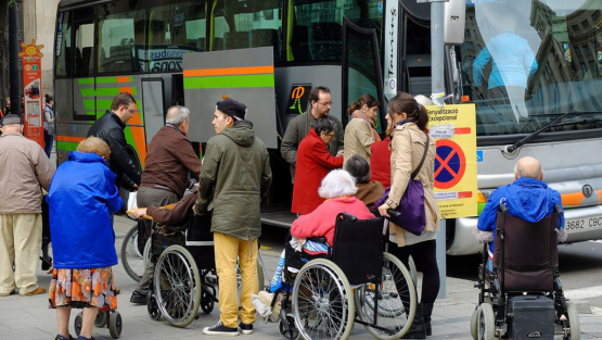 A group of elderly people with reduced mobility waiting to get on board a coach