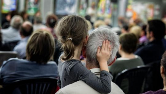 A girl sitting in the audience of a local residents' meeting puts her hand on the head of an elderly person