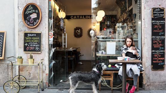 Una dona seu a la terrassa d'un cafè amb un nadó en braços i un gos al seu costat