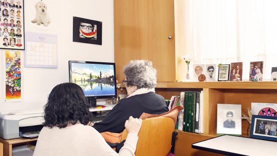 Una persona jove ajuda una persona gran a fer servir un ordinador
