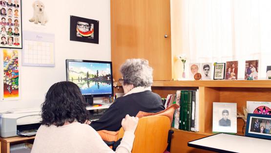 Una chica joven ayuda a una persona mayor a utilizar un ordenador