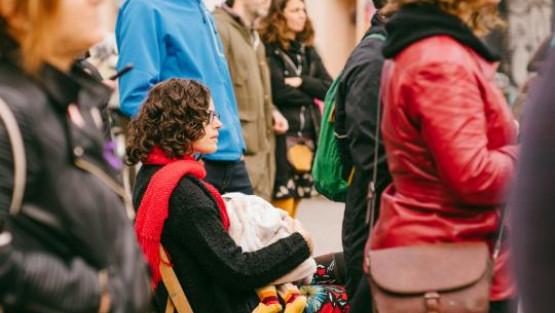 Una dona amb un nadó a la falda seu en una cadira mentre les persones del seu voltant estan dretes