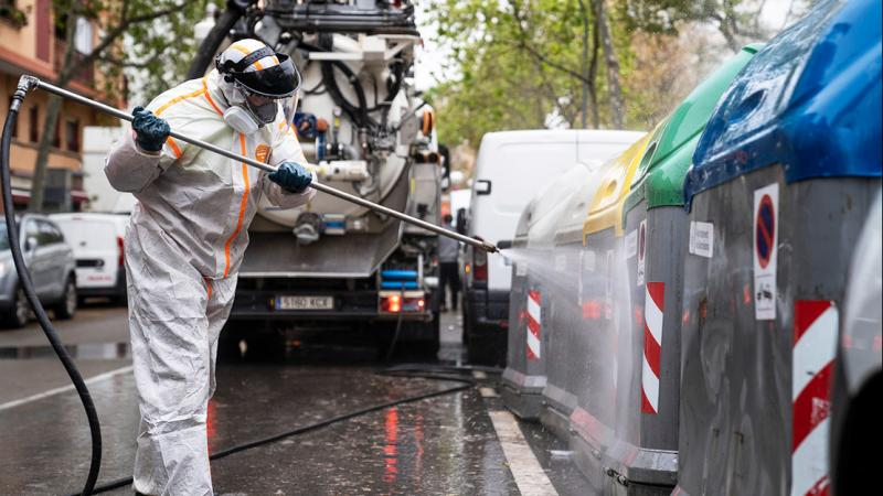 An operative from a cleaning services company uses a pressure washer to disinfect the containers.