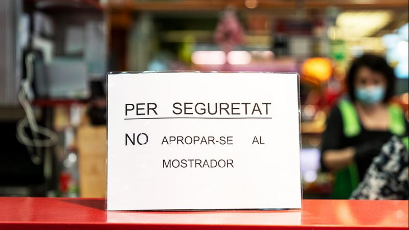 Poster on the counter of a market stall which reads: 'For safety reasons, do not approach the counter'.
