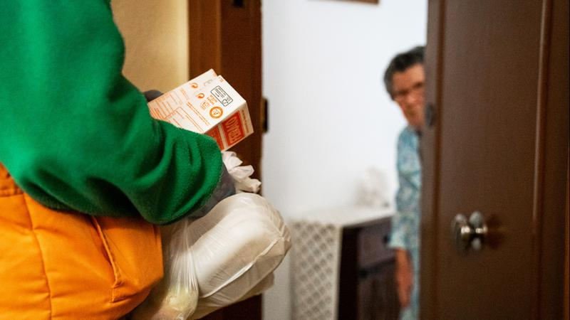 An elderly lady opens the door to a delivery person, who hands over the food package wearing gloves.