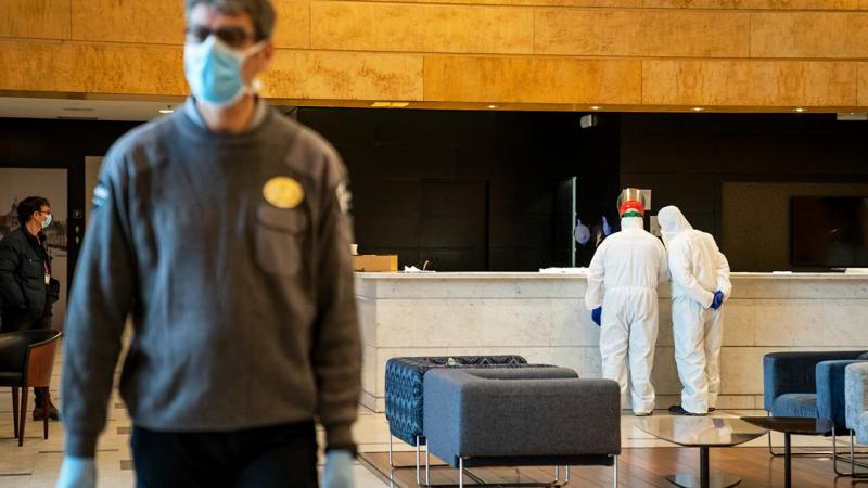 Security and healthcare personnel at Hotel Catalonia Plaza's reception. The security guard is wearing gloves and a mask, while the healthcare workers are wearing waterproof overalls, gloves and masks