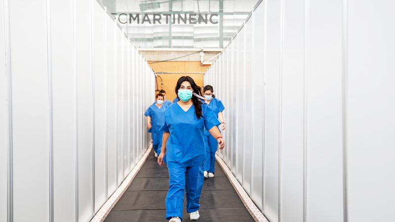 Healthcare personnel arrive at the Sports Centre and walk along one of the corridors between the panelling, which is now covered by a rubber floor