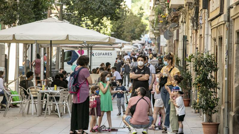 Families with children chatting on Carrer Blai, in face masks and with social distancing