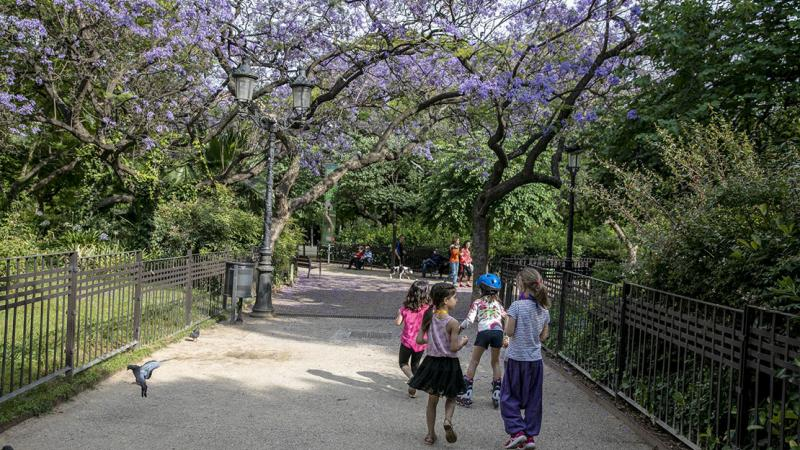 A group of young girls walk along one of the untarmacked paths on Plaça de Gaudí, surrounded by trees
