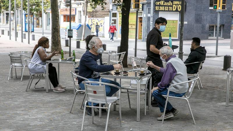 A group of elderly men with face masks are sitting in an outdoor café area about to drink the coffee that the waiter just brought them