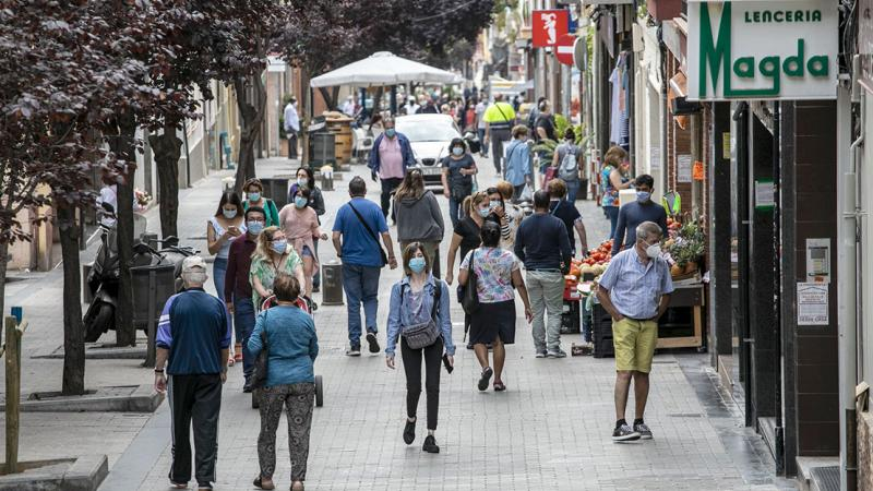General view of Carrer Joaquim Valls, with people of every age coming and going. Around it, shops are open and a few residents are doing their shopping