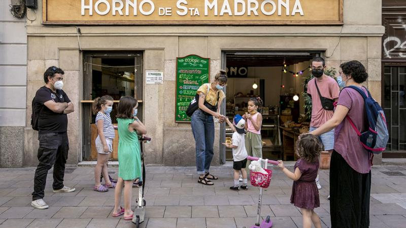 Families with children standing outside a bakery and chatting on Carrer Blai, in face masks and with social distancing