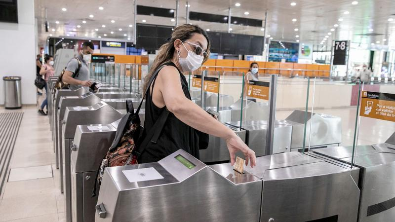 People with face masks validating their travel tickets to enter the Rodalies suburban commuter area of Sants station