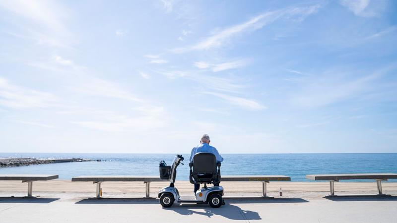 An elderly man seated on a scooter on Passeig Marítim del Bogatell looking at the sea