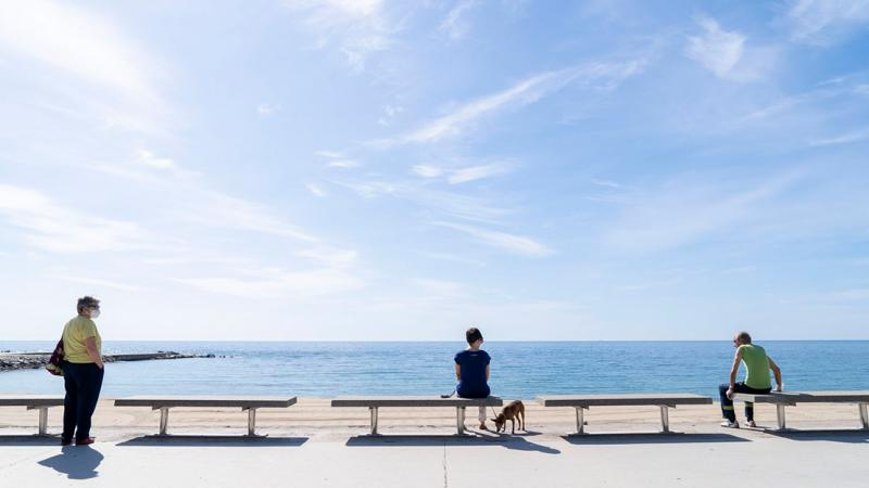 People seated on benches along Passeig Marítim del Bogatell looking at the sea and maintaining social distancing between one another