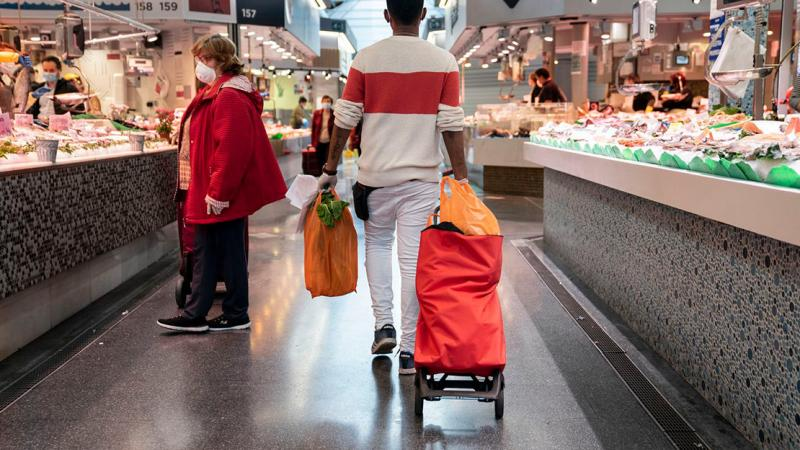 One of Mercat de Sant Antoni's home delivery service workers loaded with shopping walking through the market