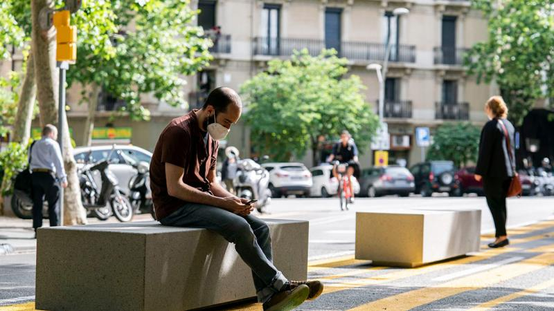 A young man with a mask consults his mobile while seated on one of the benches put up in the widened pedestrian areas on Carrer del Consell de Cent